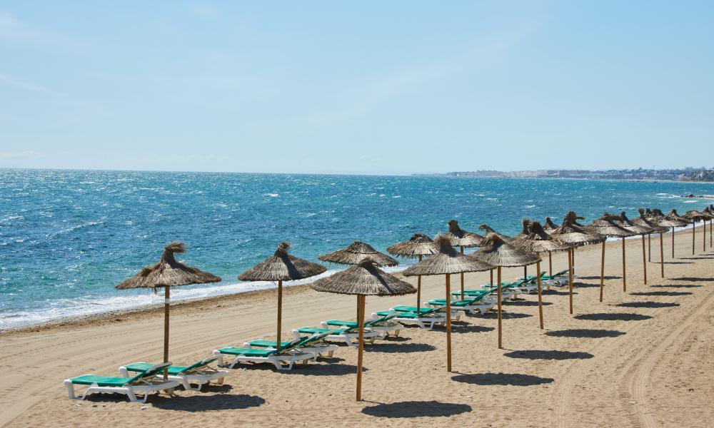 A row of empty beach umbrellas in Marbella, Spain
