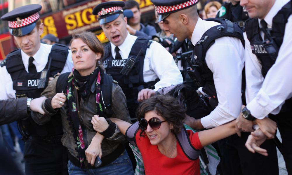 A protester outside St Paul's Cathedral is pulled away by police.