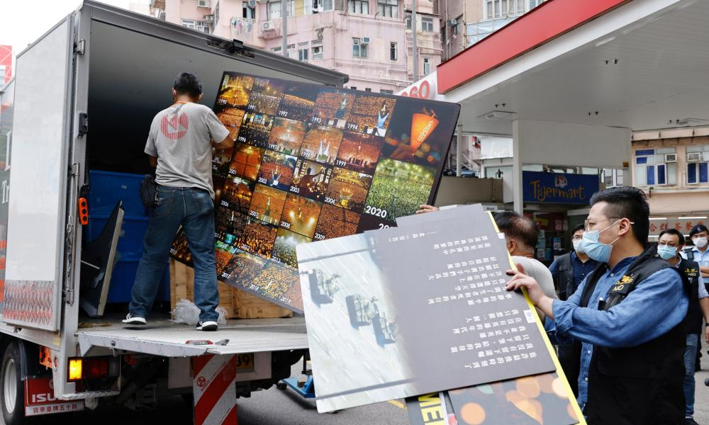 Police collect an exhibition board from the June 4th Museum, which commemorates the 1989 Tiananmen Square crackdown.