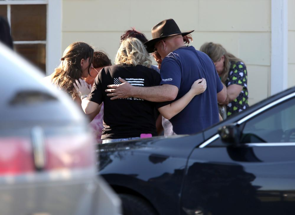 A group gathers to pray outside the Community Center in Sutherland Springs.