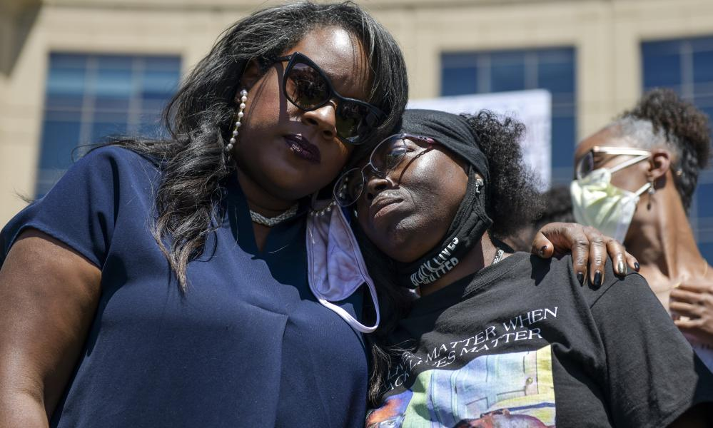 The Colorado state representative Leslie Herod, left, hugs Elijah McClain's mother, Sheneen McClain, right, as they stand with protestors on 27 June.