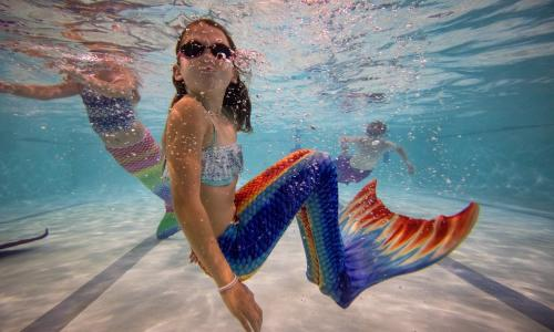 Mermaiding instructor Michelle Forsbrey speaks to her students during a Mayim Mermaid Academy lesson at the swimming pool at Bournemouth Collegiate School
