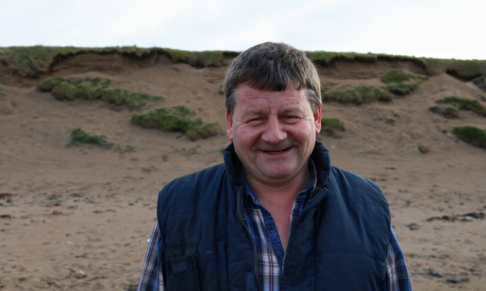 Contractor Martin Kelly stands on the beach inspecting the dunes, where he hopes a wall will be built to prevent erosion and protect the course and low-lying land from flooding.