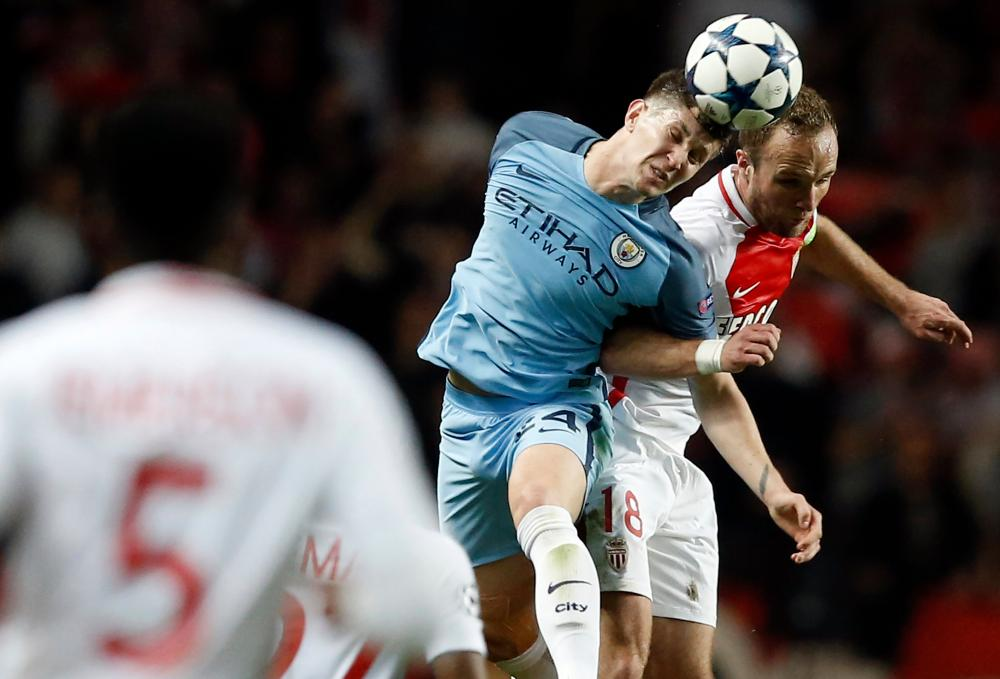 Manchester City's John Stones, left, and Monaco's Valere Germain go up for a header.