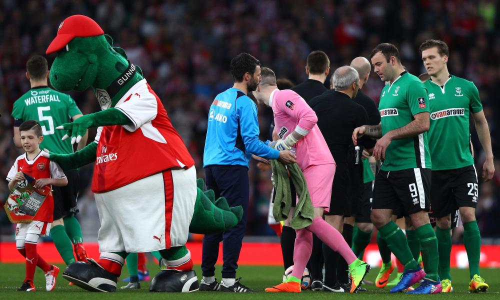 Danny Cowley manager of Lincoln City shake hands with his players as Gunnersaurus shuffles off the pitch.