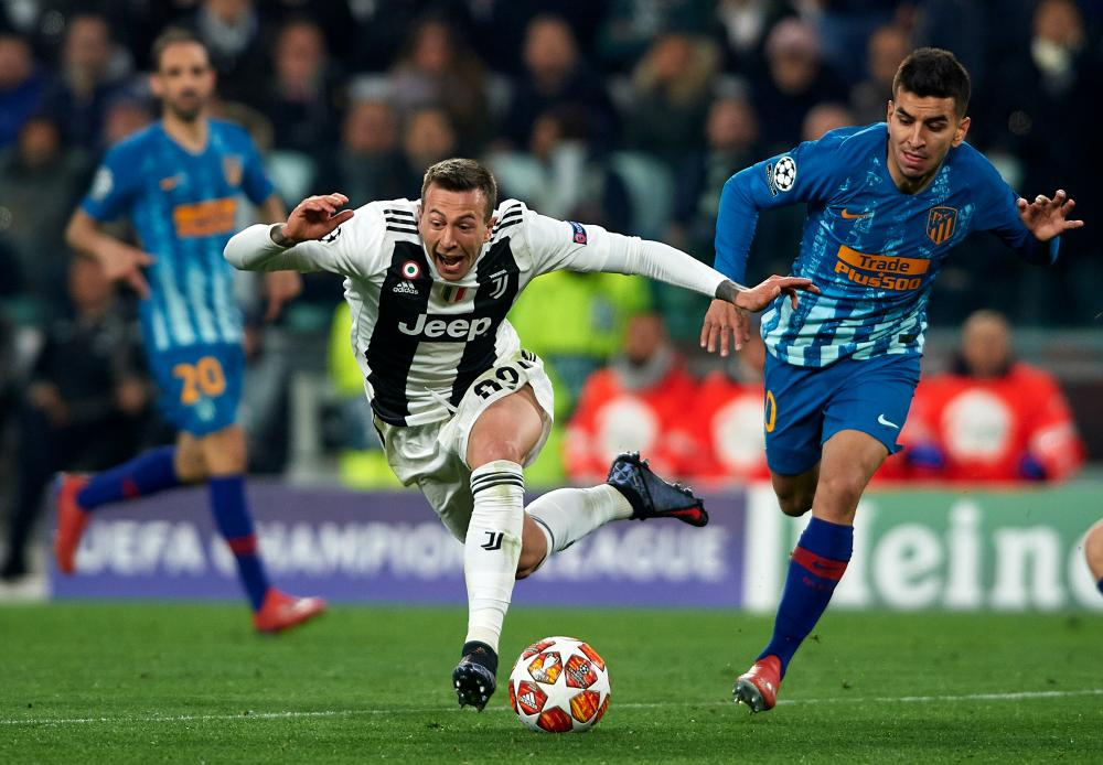 Atletico's Angel Correa, right, pushes Juventus' Federico Bernardeschi in the back to give away a penalty. What an idiot.