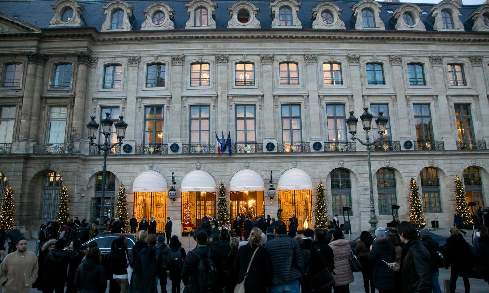 People gather outside the newly reopened Paris Ritz as Chanel stages its shows inside.