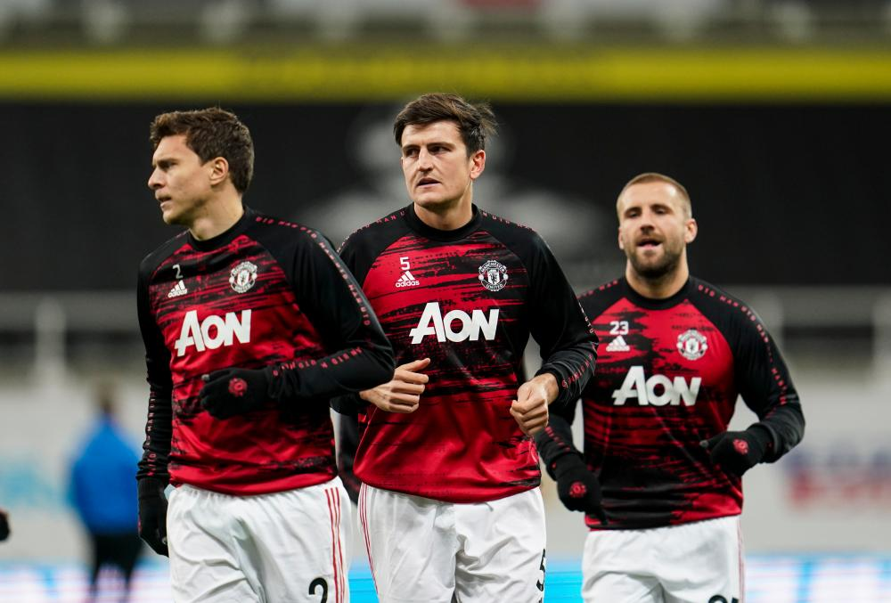 Harry Maguire of Manchester United (centre) warms up