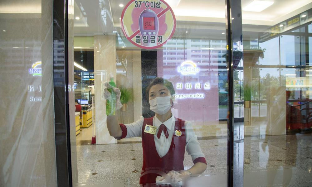 A cashier sprays disinfectant onto a window as part of preventative measures against Covid-19, in the Daesong Department Store in Pyongyang on September 27, 2021.