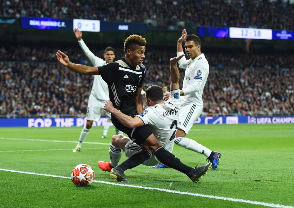 David Neres of Ajax and Daniel Carvajal of Real Madrid battle for the ball.