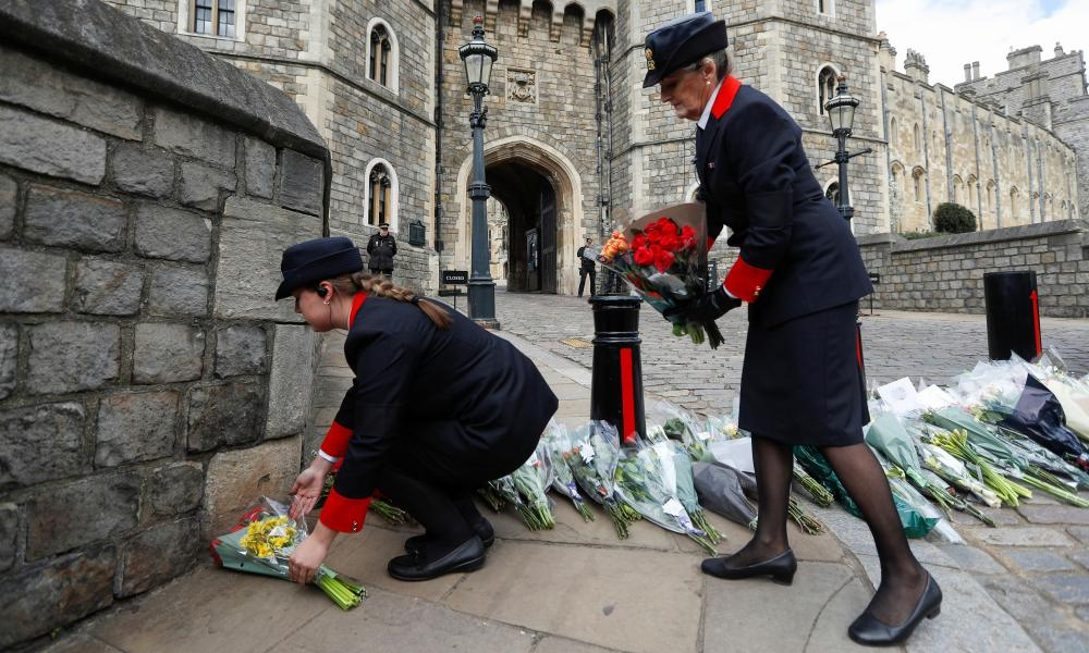 Windsor Castle wardens move flowers placed by members of the public