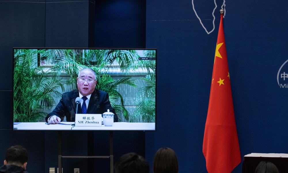A screen showing Xie Zhenhua, China's special envoy for climate change, speaking during a media briefing.