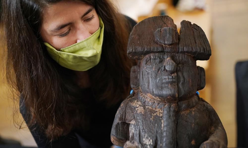 Collection manager Ana Carreira Galban holds a wooden figure depicting a bound prisoner with a headdress and rope around his neck, from the Moche people, dating AD100-800.