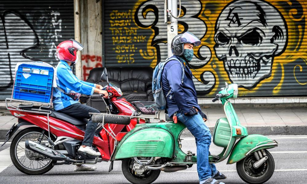A man riding a scooter waits on a traffic light in front of graffiti on a store's shutters in downtown Bangkok.