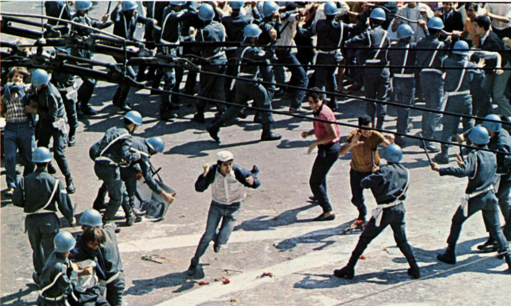 A man waving both fists runs through a phalanx of riot police, seen from above