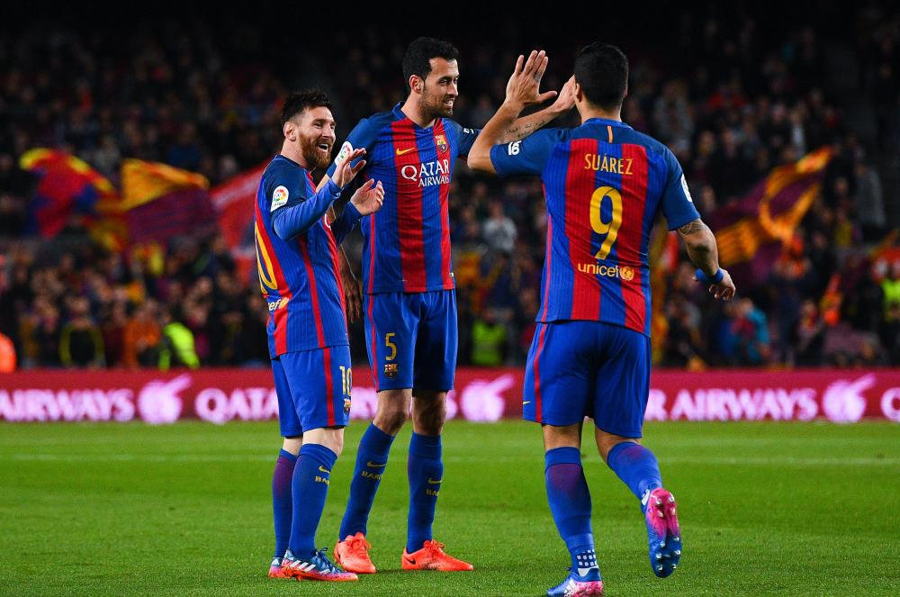 Messi, left, celebrates his goal with team-mates Sergio Busquets and Luis Suarez.