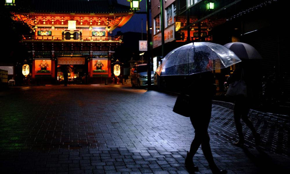 Pedestrians walk with umbrellas in front of the entrance of Kanda Shrine in Tokyo on 11 June 2020.