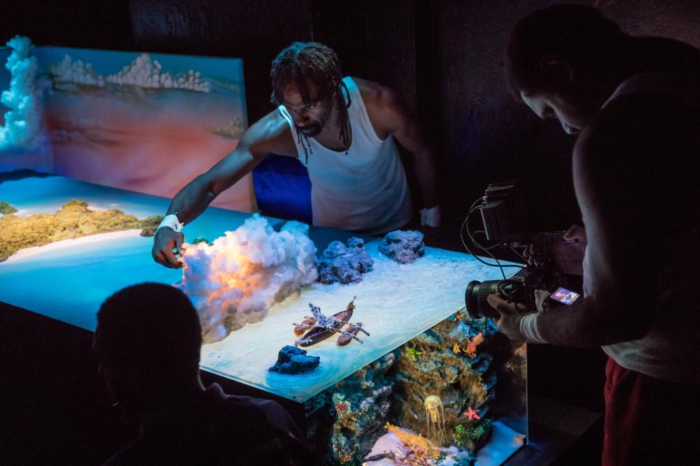 A diorama of under-the-sea, being filmed by a cast member for projection.