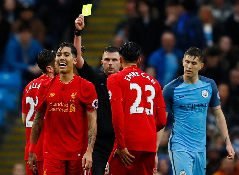 Liverpool's Roberto Firmino is shown a yellow card by referee Michael Oliver