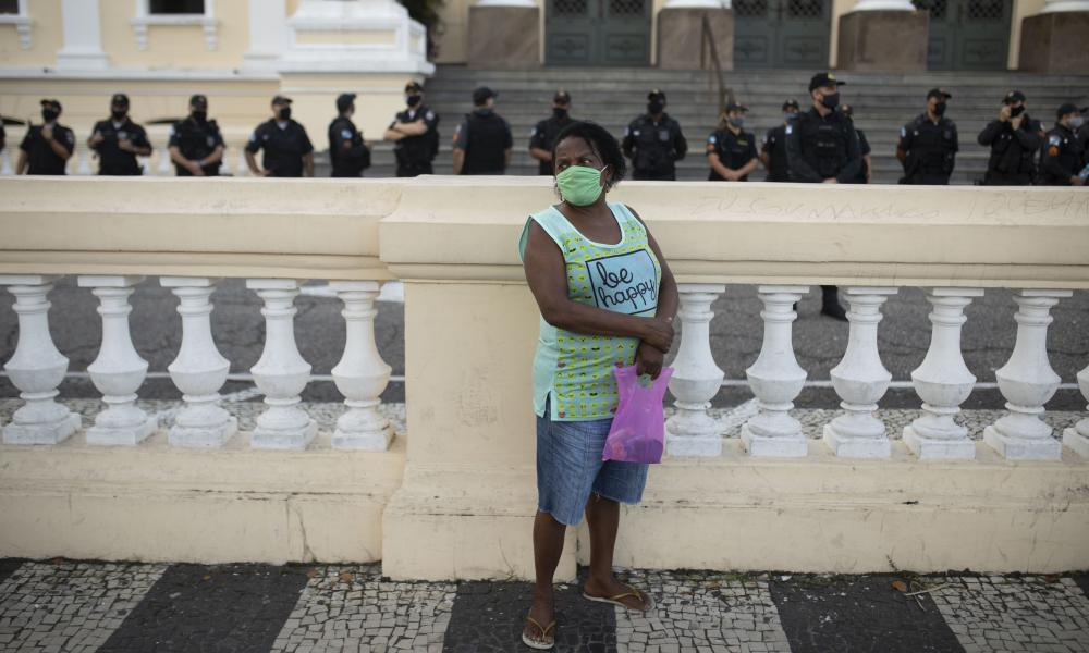 A woman wearing a face mask stands near Black Lives Matter protests in the Metropolitan Region of Rio de Janeiro, Brazil.