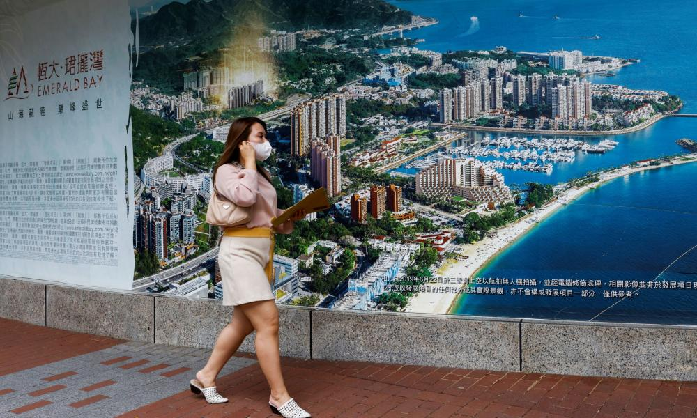 A woman walks past an advertisement for a property development by Evergrande in Emerald Bay in Hong Kong.