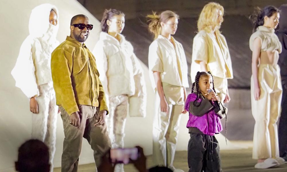Kanye West and models at his Yeezy show listen as his six-year-old daughter North takes to the stage.