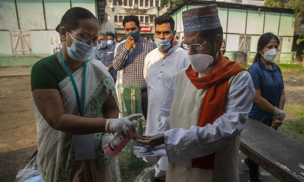A health worker gives sanitizer to an Indian voter standing in the queue to vote in Gauhati, India.