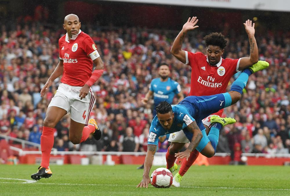 Theo Walcott is brought down just outside the box by Benfica's Eliseu.