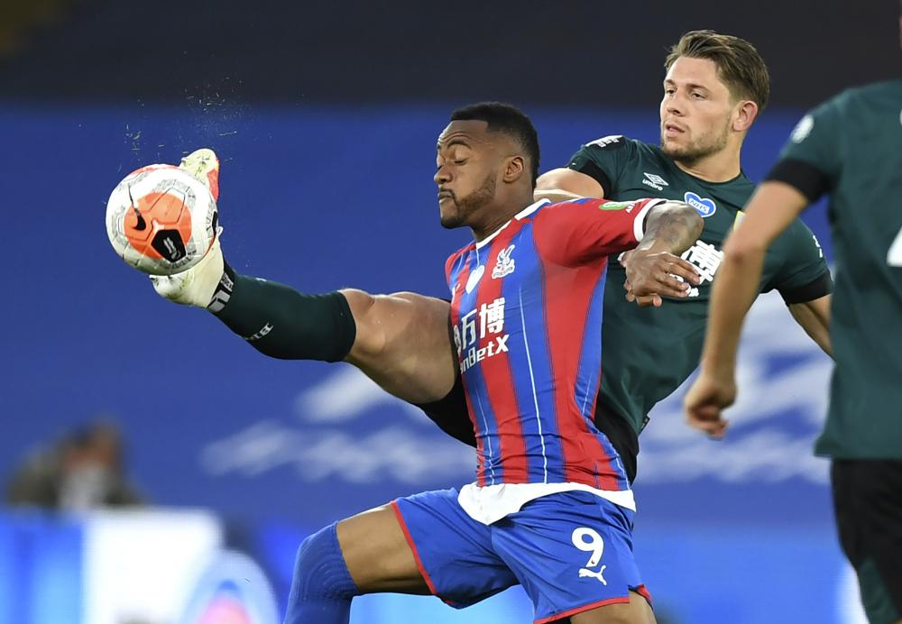 Burnley's James Tarkowski kicks the ball away from Crystal Palace's Jordan Ayew.