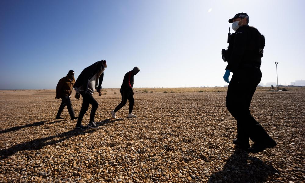 Immigration police process migrant arrivals on Dungeness beach in Kent.