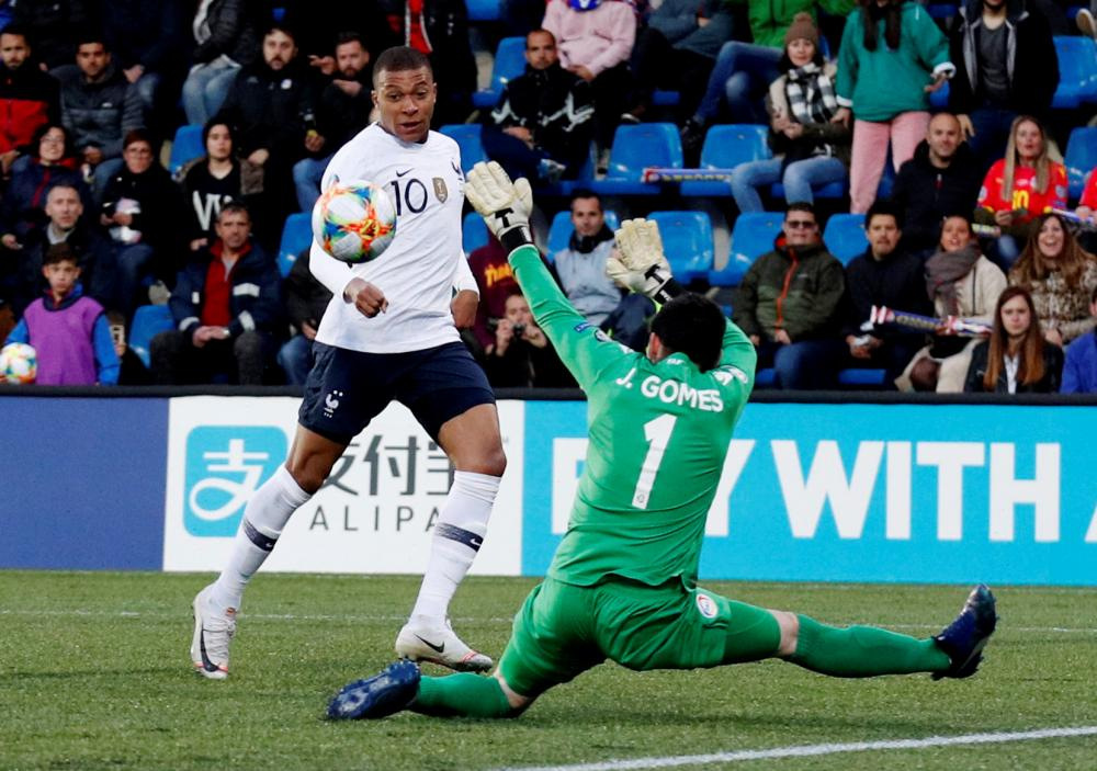 France's Kylian Mbappe scores their first goal.