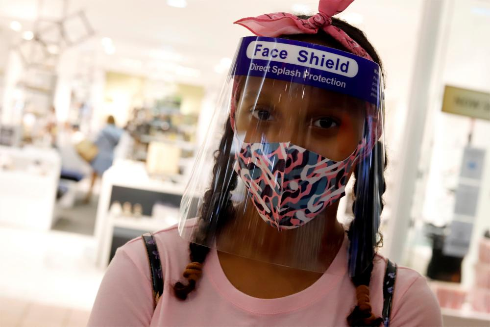 A woman uses a facial mask and a protective face shield at the Plaza Las Americas shopping centre in San Juan, Puerto Rico.