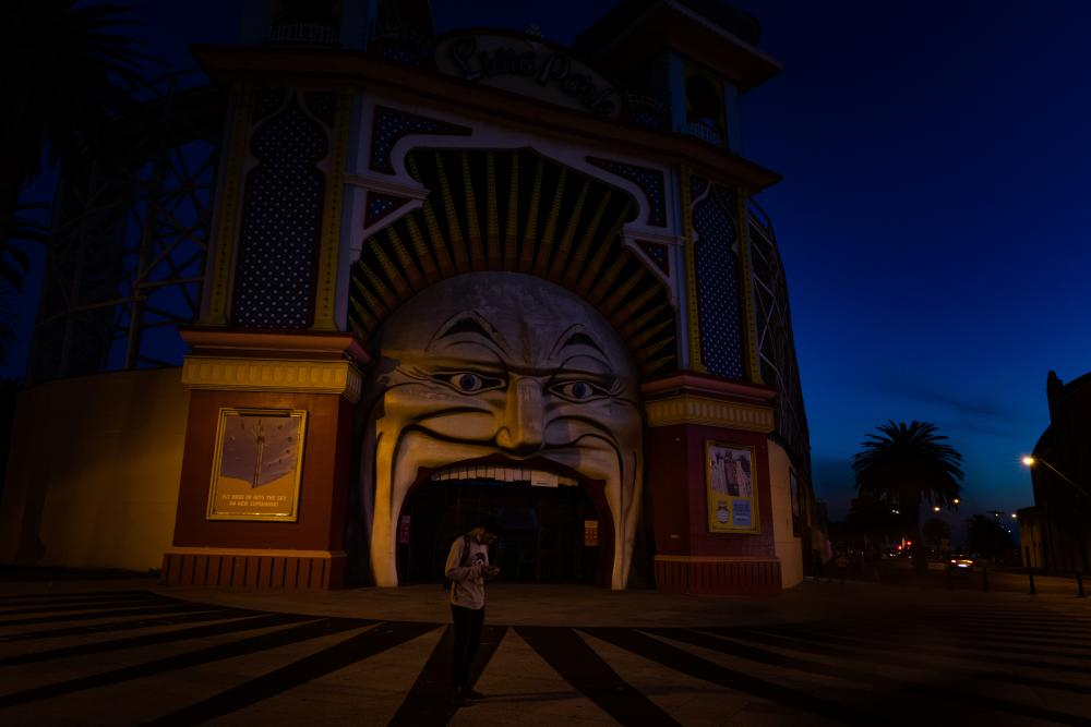 A man outside a deserted Luna Park as curfew approaches in Melbourne on 10 September.