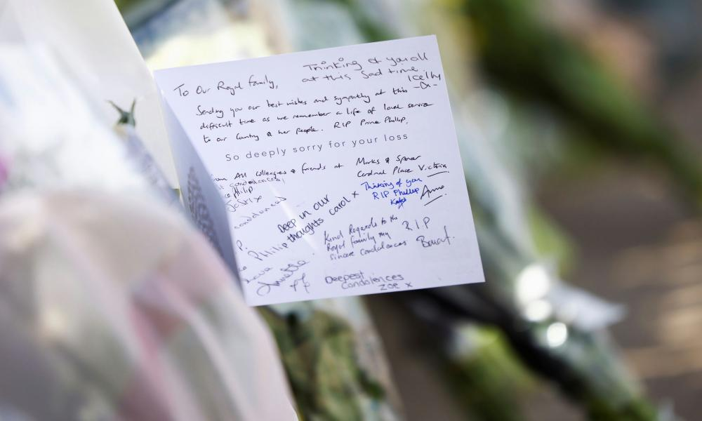 A message on a bouquet of flowers is seen outside Buckingham Palace.