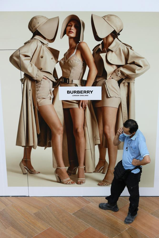A man wearing a protective mask in Singapore speaks on the phone in front of a Burberry advertising billboard