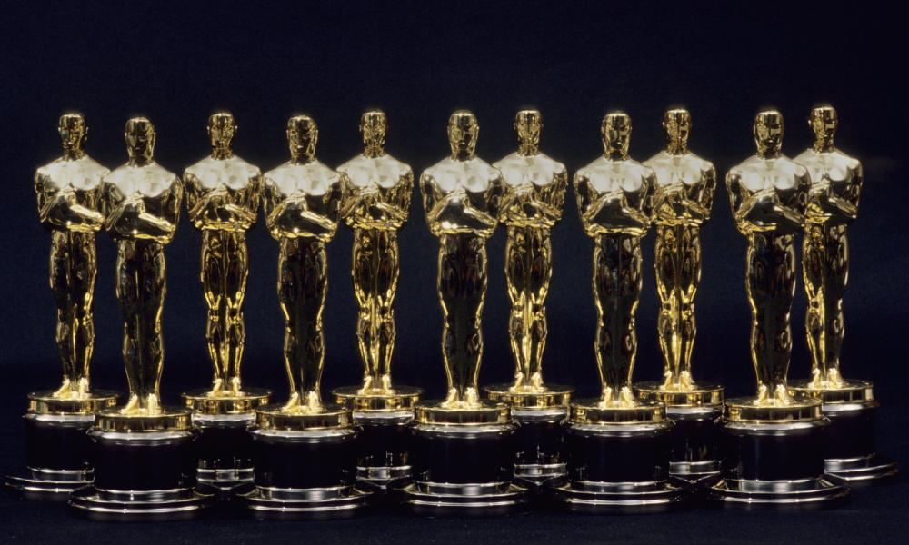 Eleven golden Oscar statuettes in a line