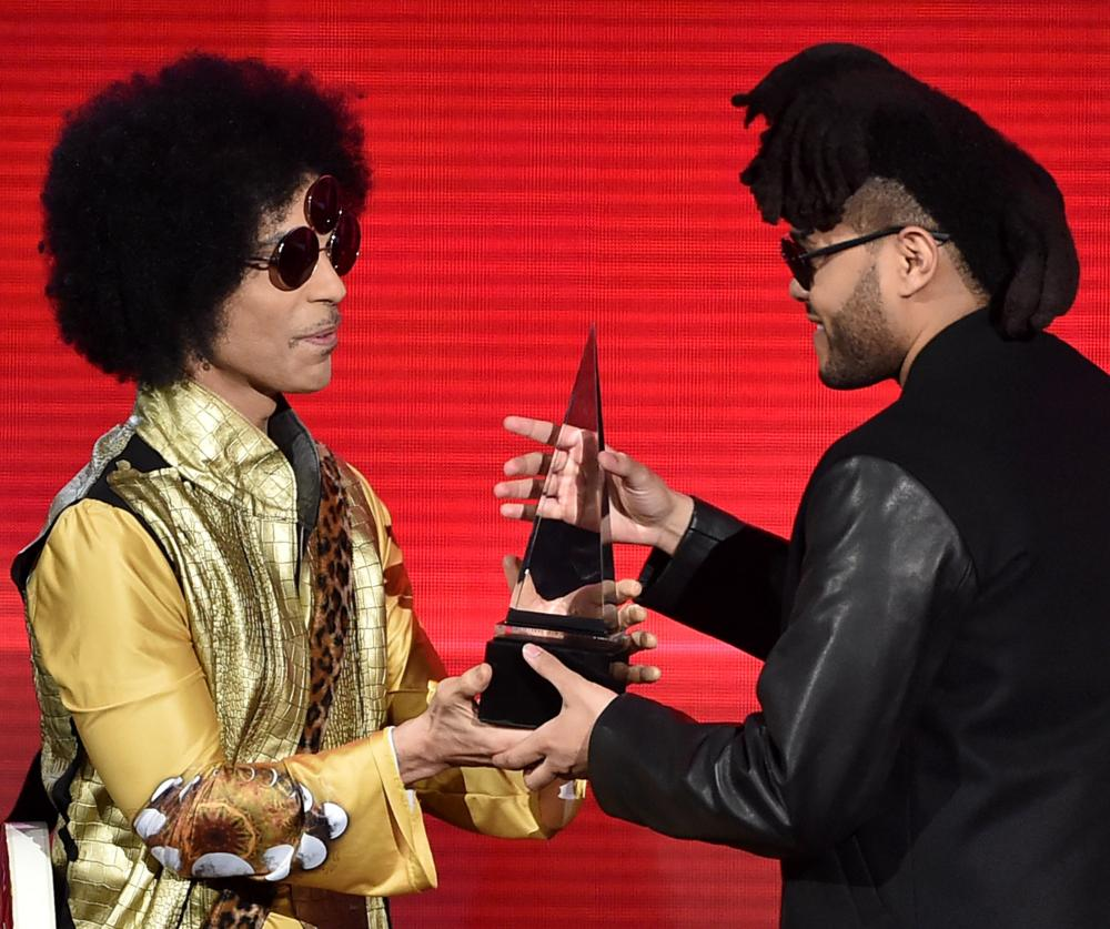 Musician the Weeknd receiving an award from Prince  at the American Music awards 2015