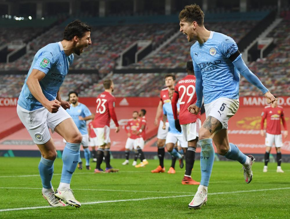 Manchester City's John Stones (right) celebrates scoring their first goal with Ruben Dias.