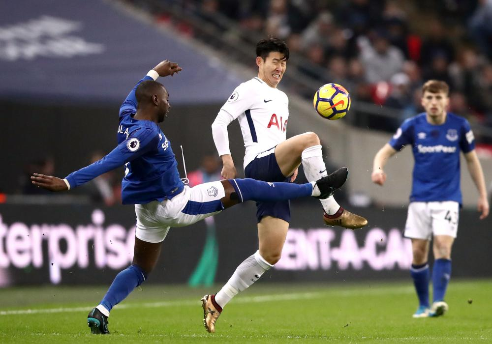 Tottenham Hotspur's Son Heung-Min and Everton's Yannick Bolasie, left, battle for the ball.