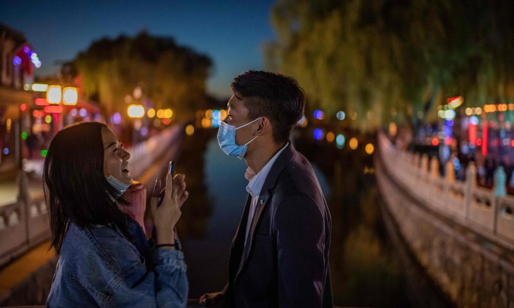 A couple in facemarks on the Hu Hai lake in Beijing.