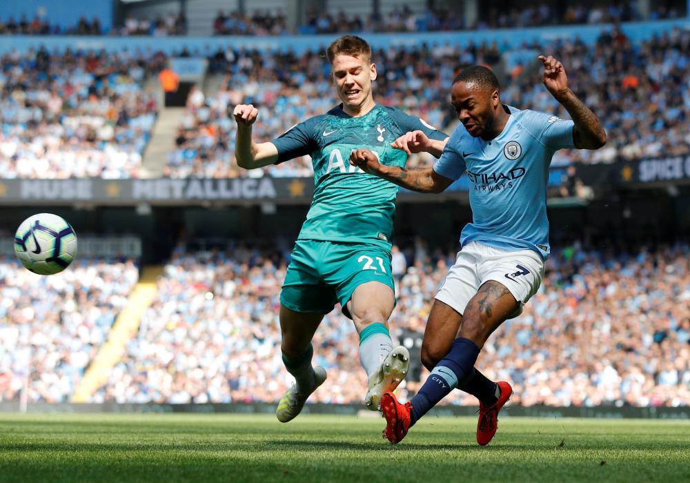 Manchester City's Raheem Sterling puts in a cross despite pressure from Tottenham's Juan Foyth.