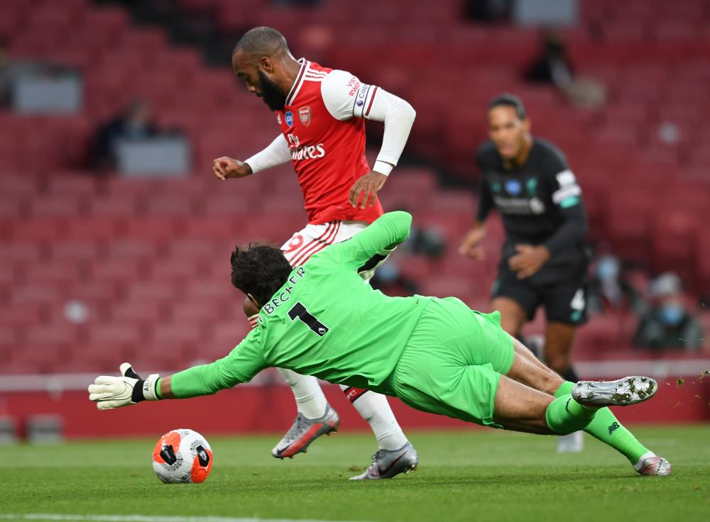 Alexandre Lacazette rounds Alisson before scoring Arsenal's first goal.