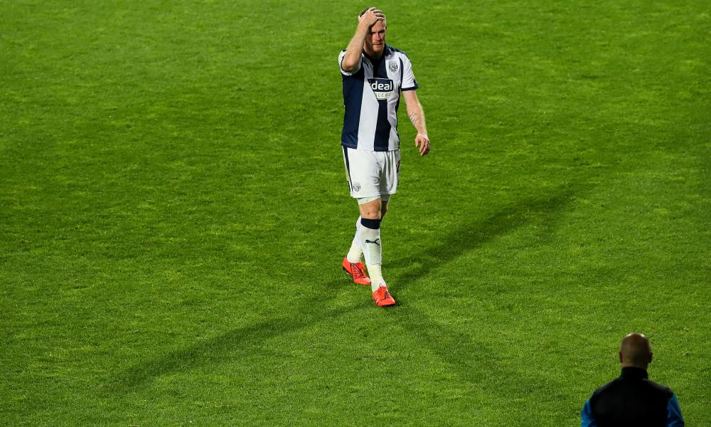 A dejected Chris Brunt of West Bromwich Albion walks off the pitch after receiving a red card.