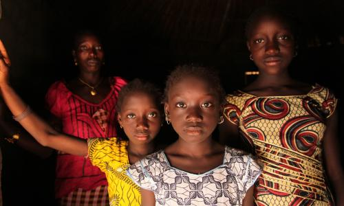 Shows a woman and her daughters standing in their home, in the village of Cambadju in Bafata Region, Guinea-Bissau.