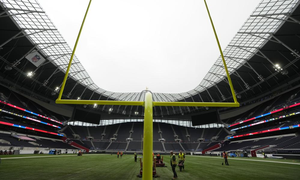 Workers prepare the pitch at the Tottenham Hotspur Stadium for the two NFL games