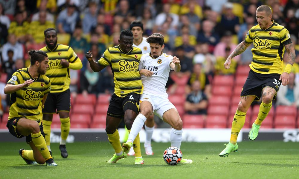 Wolves' Francisco Trinçao battles for possession with Peter Etebo of Watford.