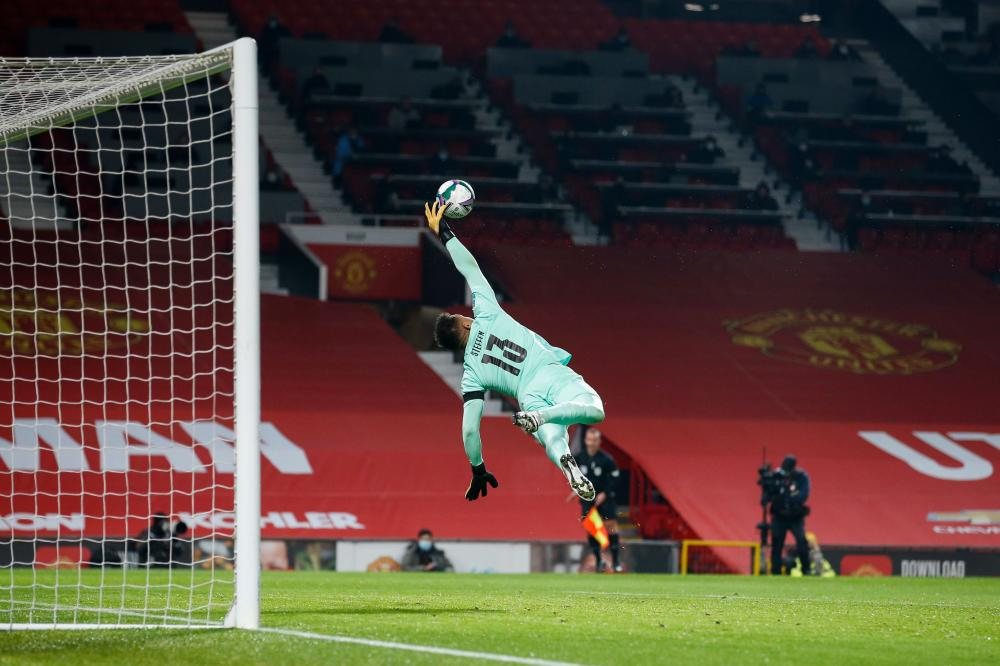 A flying Zack Steffen at full stretch denies United's Bruno Fernandes.