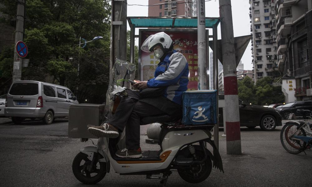 A courier sits on a bike waiting for orders on 2 April in Wuhan. The government stipulates that residents with green health code can go out in public.