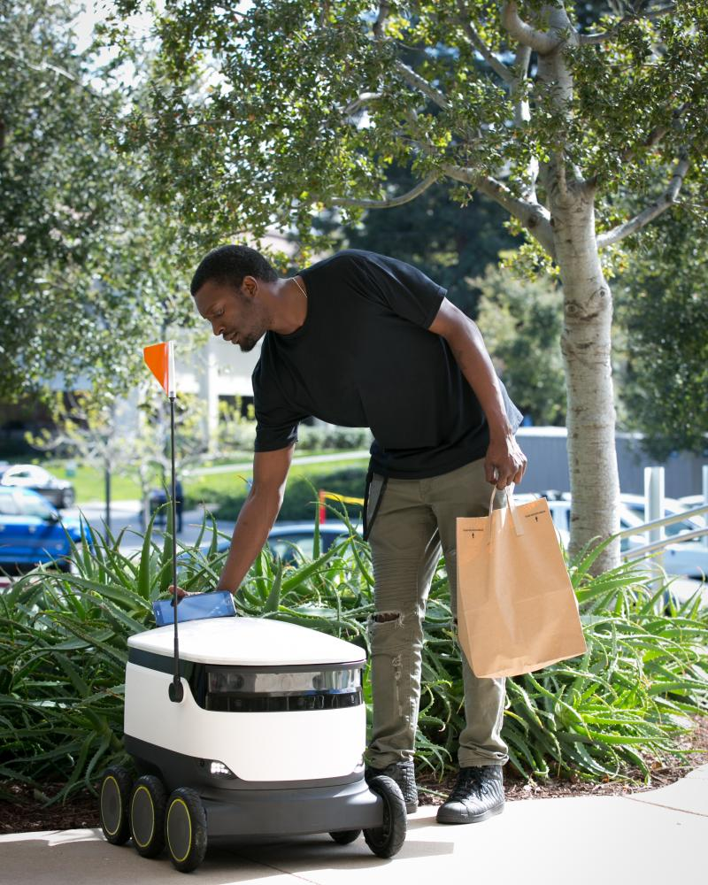 An Intuit employee gets his delivery from a Starship robot.