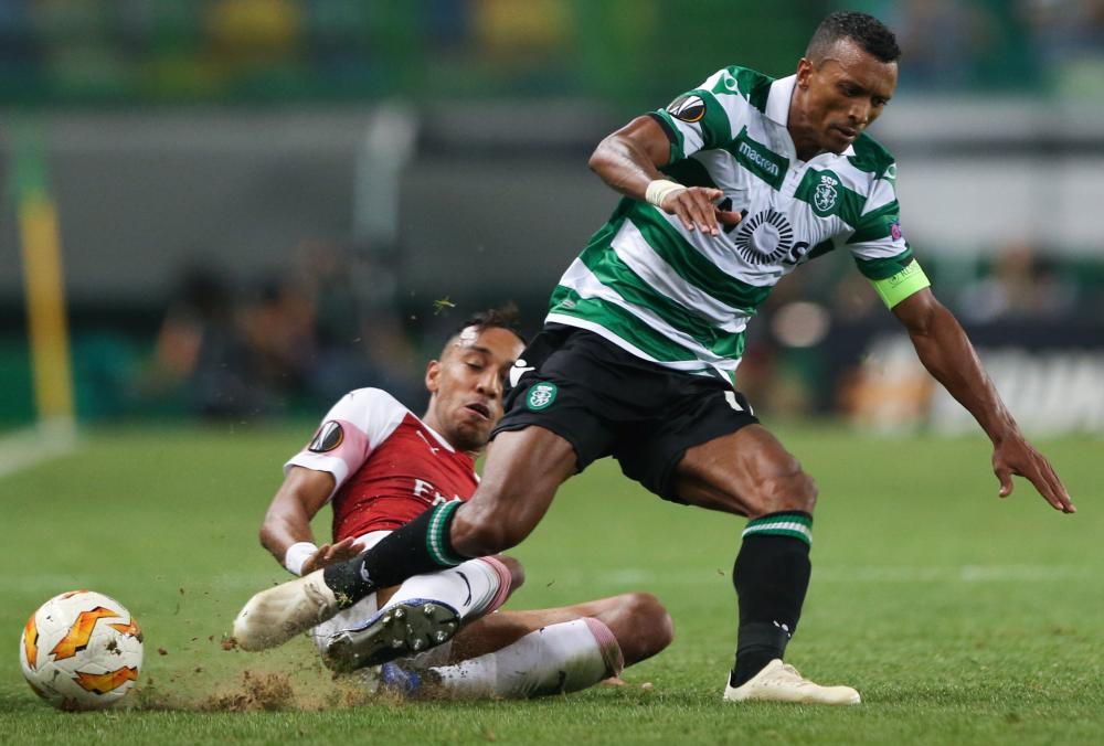 Sporting's Nani is tackled by Arsenal's Pierre-Emerick Aubameyang.